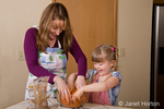 Mother and daughter laughing while mixing brown sugar and grated carrots in mixing bowl, while making carrot cake