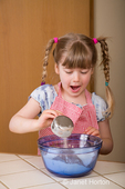 Five year old girl pouring sugar into mixing bowl, with an astonished look on her face, as she helps make carrot cake