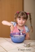 Five year old girl mixing dry ingredients of a carrot cake in a mixing bowl 