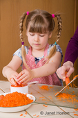 Woman grating carrots, with 5 year old daughter watching, to make a carrot cake