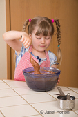 Five year old girl stirring batter of a chocolate bundt cake