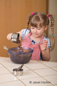 Five year old girl pouring chocolate chips into a chocolate bundt cake in mixing bowl