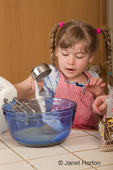 Five year old girl pouring sugar into mixing bowl,  as she helps make carrot cake