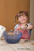 Five year old girl using measuring spoons to measure vanilla extract and add it to a chocolate bundt cake batter in a mixing bowl