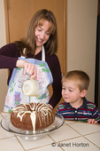Mother pouring white chocolate glaze onto chocolate bundt cake while three year old son watches
