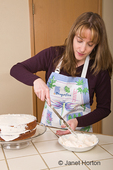Woman frosting a carrot cake on a glass cake stand with cream frosting