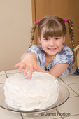 Five year old girl placing her finger in the middle of cream frosting of a carrot cake, trying to sneak a bite of frosting
