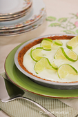 Key lime pie with slices of twisted lime, in a pie pan on plates, on a floral design tablecloth, with china plates in the background