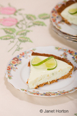 Slice of key lime pie, with a twisted lime slice on top, resting on a china plate on a tablecloth with a floral pattern