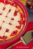 Baked cherry pie with pie server on a floral design cloth tablecloth with a red cloth napkin