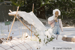Snow-covered scarecrow, garden and leaning trellis