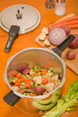 Raw pork chops and vegetables in pressure cooker, ready to cook, with extra celery, red potatoes, red onion, carrots, salt and pepper sitting beside it on a wood table