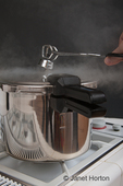 Pressure cooker on a stove with steam escaping as a woman uses tongs to remove the top to let the steam escape