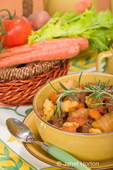 Bowl of Hungarian Goulash with csipetke with a sprig of rosemary on it, resting on a plate with a spoon, with a basket of raw vegetables on a floral placemat