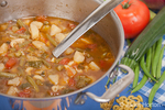 Pot of homemade vegetable soup containing tomatoes, green beans, onion, zuchinni, potatoes and pasta, with the raw vegetables as well as a soup ladle