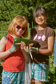 Two girls (eight and ten) holding a large freshly harvested green zucchini from their own plot in a community garden