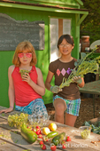 Two girls (ages eight and ten) showing their harvest of broccoli gone to flower, strawberries, zucchini, lemon cucumber and peas, in front of a pincic table at a community pea patch garden