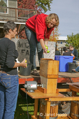 Woman adding an apple to an automated cider press, at a cider pressing party