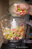 Adding raw ingredients (bell peppers, onions, cabbage, carrots and green tomatoes) for making relish into a blender