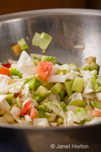 Large metal bowl of chopped raw ingredients (bell peppers, onions, cabbage, carrots and green tomatoes) for making relish