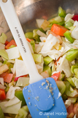 Metal bowl of chopped raw ingredients (bell peppers, onions, cabbage, carrots and green tomatoes) for making relish, with a spatula
