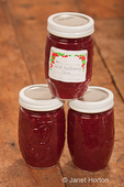 Three jars of wild huckleberry jam on a rustic wood tabletop in a studio setting