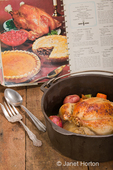 Dutch-style roasted chicken with baked red potatoes, carrots and celery, in a cast iron pot on a rustic wood table, with an old cookbook in the background