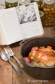 Dutch-style roasted chicken with baked red potatoes, carrots and celery, in a cast iron pot on a rustic wood table, with an old cookbook and canned goods in the background