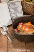 Dutch-style roasted chicken with baked red potatoes, carrots and celery, in a cast iron pot on a rustic wood table, with an old cookbook, basket and canned goods in the background