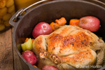 Dutch-style roasted chicken with baked red potatoes, carrots and celery, in a cast iron pot on a rustic wood table, with canned goods in the background