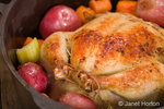 Dutch-style roasted chicken with baked red potatoes, carrots and celery, in a cast iron pot on a rustic wood table