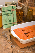 Baked candied sweet potatoes in a rectangular baking dish on a rustic wood tabletop with an old cookbook, antique whisk, canned goods and basket in the background
