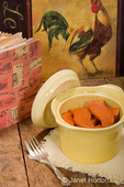 Baked candied sweet potatoes in an antique round casserole bowl resting on a cloth napkin, on a rustic wood tabletop with an old cookbook and chicken artwork in the background