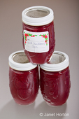 Three jars of homemade wild huckleberry jam, with one stacked on top of the other two, made from red huckleberries