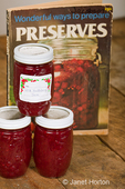 Three jars of homemade wild huckleberry jam, made from red huckleberries, with an old cookbook