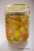 Jar of home-canned sweet pickles, showing the pickled cucumbers, red peppers and onions