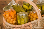 Home-canned produce (Rainier cherries and dill pickles) in a large wicker basket resting on a rustic wood tabletop