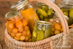 Home-canned produce (Rainier cherries, butternut squash soup and dill pickles) in a large wicker basket resting on a rustic wood tabletop
