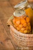Home-canned produce (Rainier cherries and butternut squash soup) in a large wicker basket resting on a rustic wood tabletop