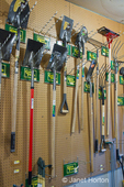 Small, local, independent hardware store wall display of shovels, rakes and pitchforks hung on a pegboard, at Madison Park Hardware store