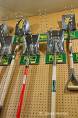 Small, local, independent hardware store wall display of shovels hung on a pegboard at Madison Park Hardware store