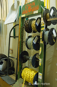 Small, local, independent hardware store rack with coils of various weight chains at Madison Park Hardware store