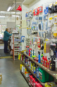 Small, local, independent hardware store interior wall display of small hardware items and sales people at Madison Park Hardware store