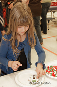 Six year old girl decorating a gingerbread man cookie at a craft festival in an elementary school gymnasium / lunchroom