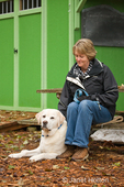 Woman sitting on picnic table by a garden shed, next to Murphy, an English Yellow Labrador Retriever, who is relaxing