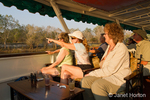 People enjoying a sundowner cruise, with one woman pointing at an animal on shore