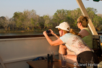Women photographing animals on shore, on a sundowner cruise