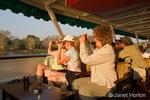 Women photographing animals on shore, on a sundowner cruise