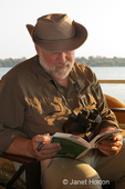 Man looking at wildlife identification guide on a sundowner cruise
