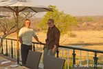 Man and woman in outside dining area beside game preserve at the Stanley and Livingstone Hotel